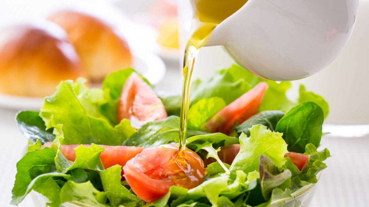 someone pouring an oil based dressing onto a salad