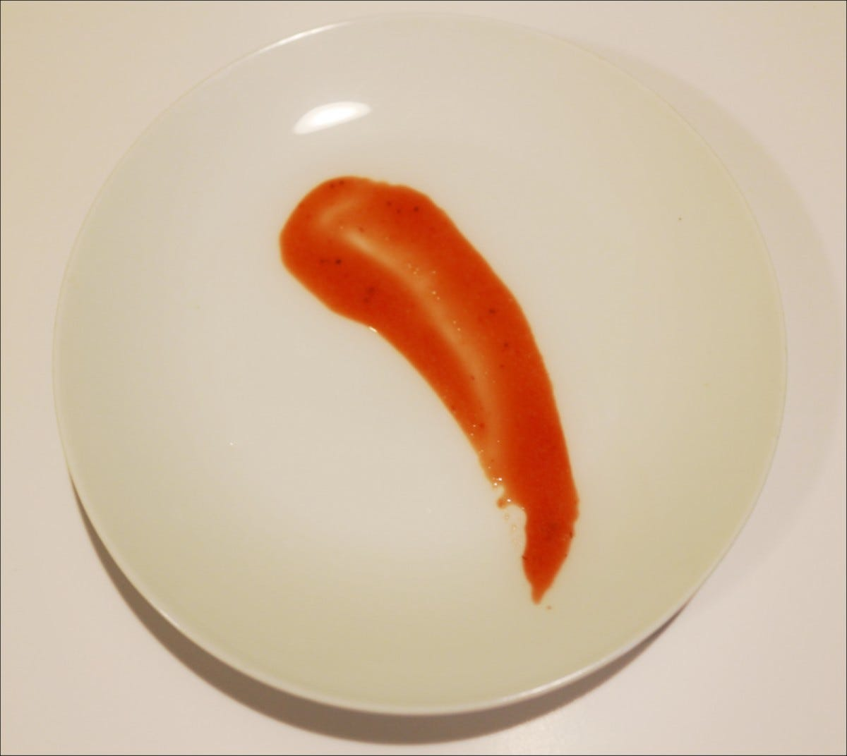 Strawberry puree design created by dragging the bottom part of a spoon across the white plate.