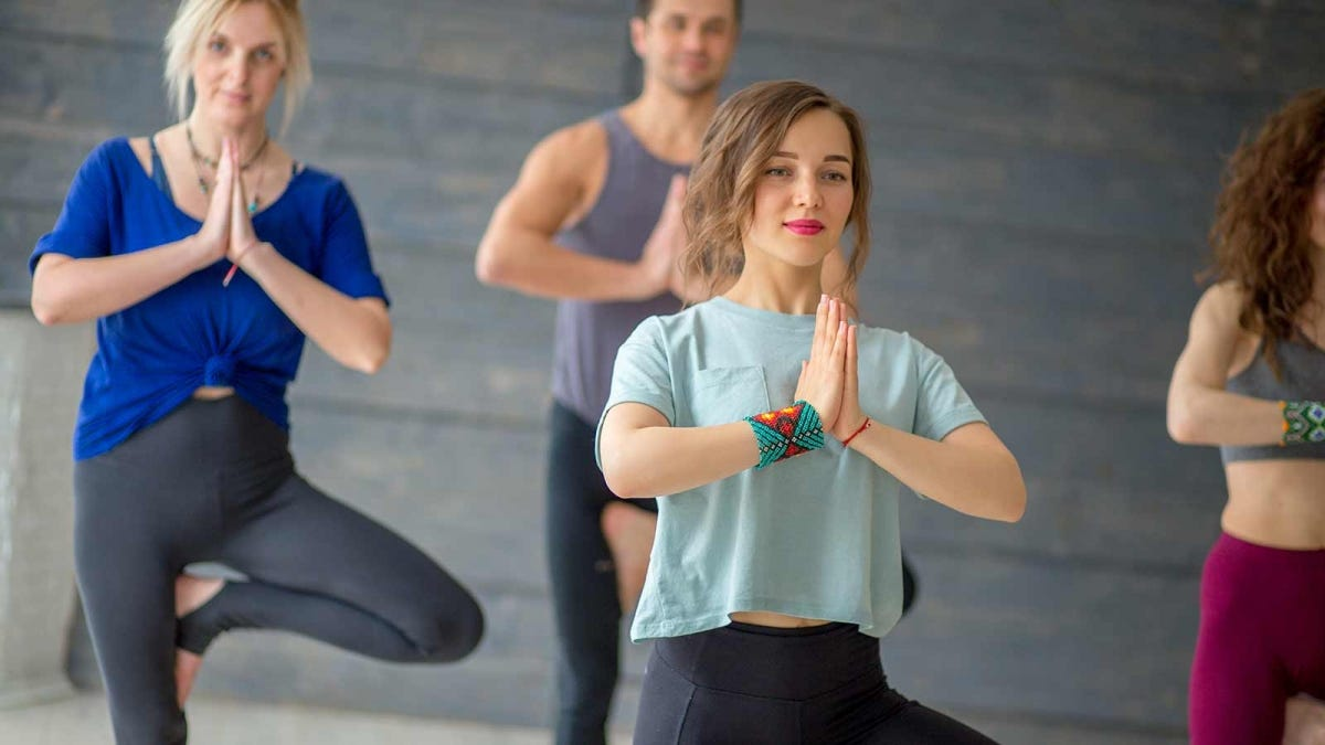 a group of young people practicing yoga in a studio
