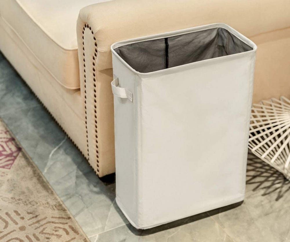 Slim beige laundry hamper next to a beige couch