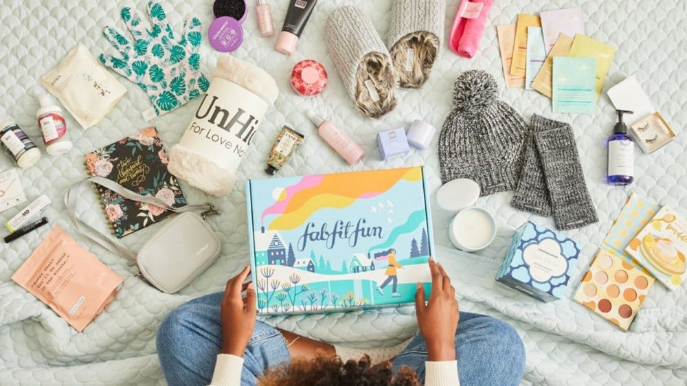 A woman holding a fabfitfun box, with the contents spread around her on a bed.