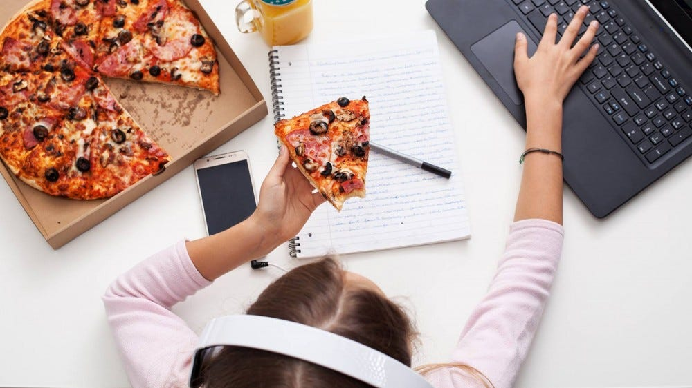 A young girl eating pizza while checking her reading rewards on a laptop.