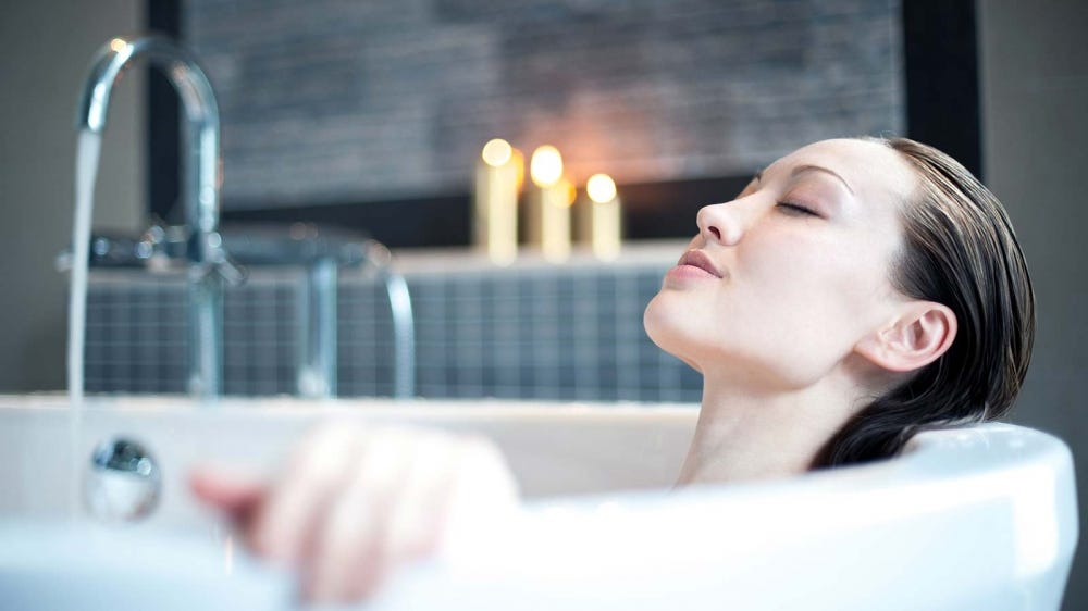 A woman relaxing by candlelight in a bathtub.