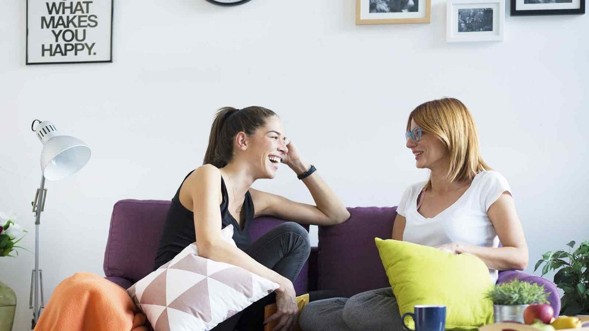 A woman and her long term guest chatting on the couch