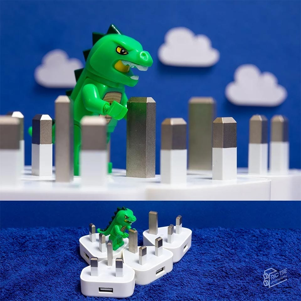 Miniature composition showing a toy Godzilla attacking a city made of power adapter prongs.