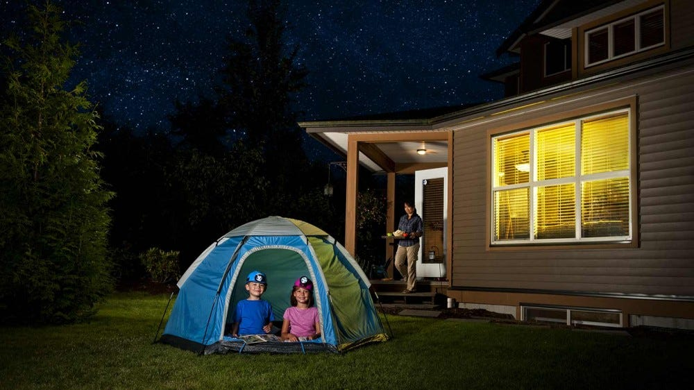Two kid camping out in a tent in the backyard.