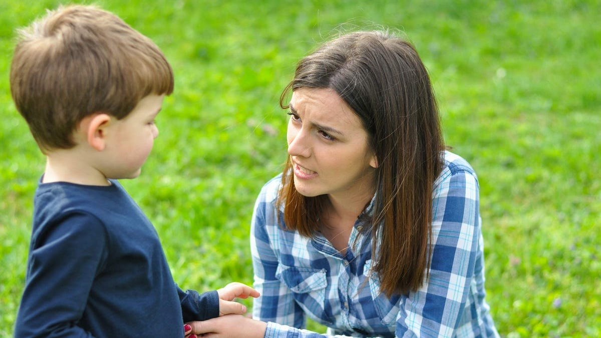 A woman talking to a little boy.