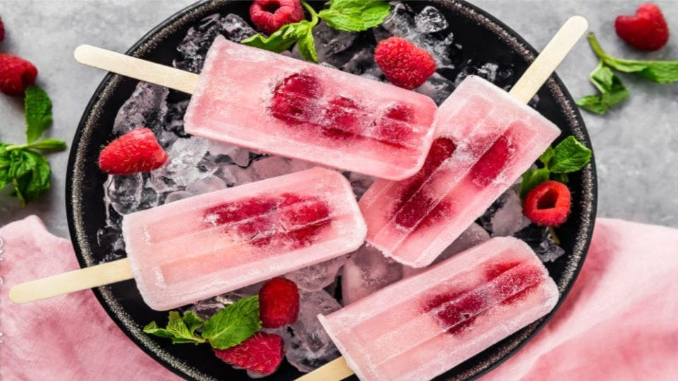 Four Raspberry Gin Fizz Popsicles sitting on ice, surrounded by mint leaves and raspberries.