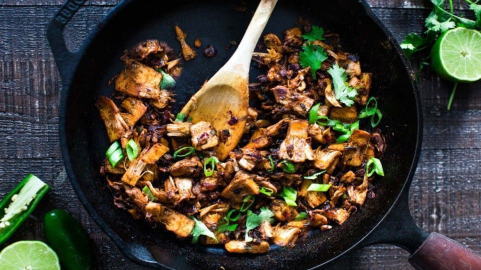 A cast iron skillet filled with jackfruit carnitas, with lime and jalapenos on the side.