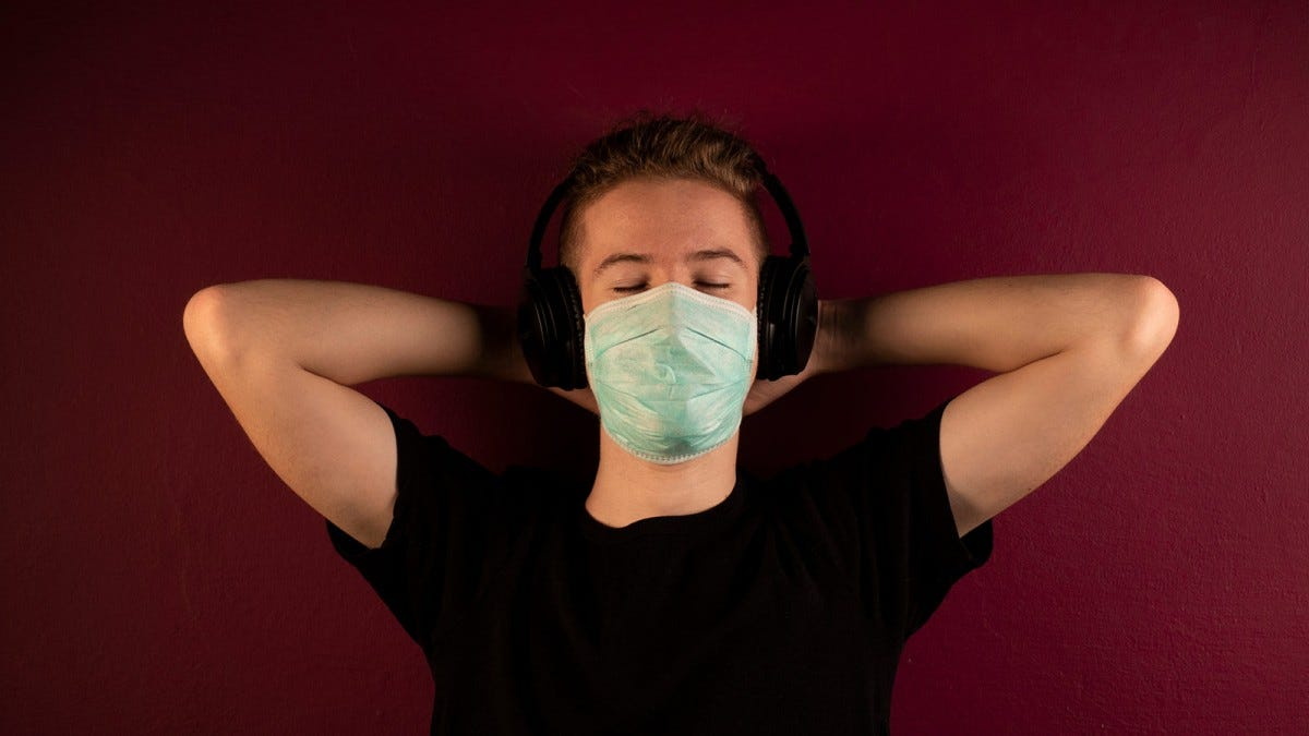 Young man listening to music with headphones while wearing a mask.
