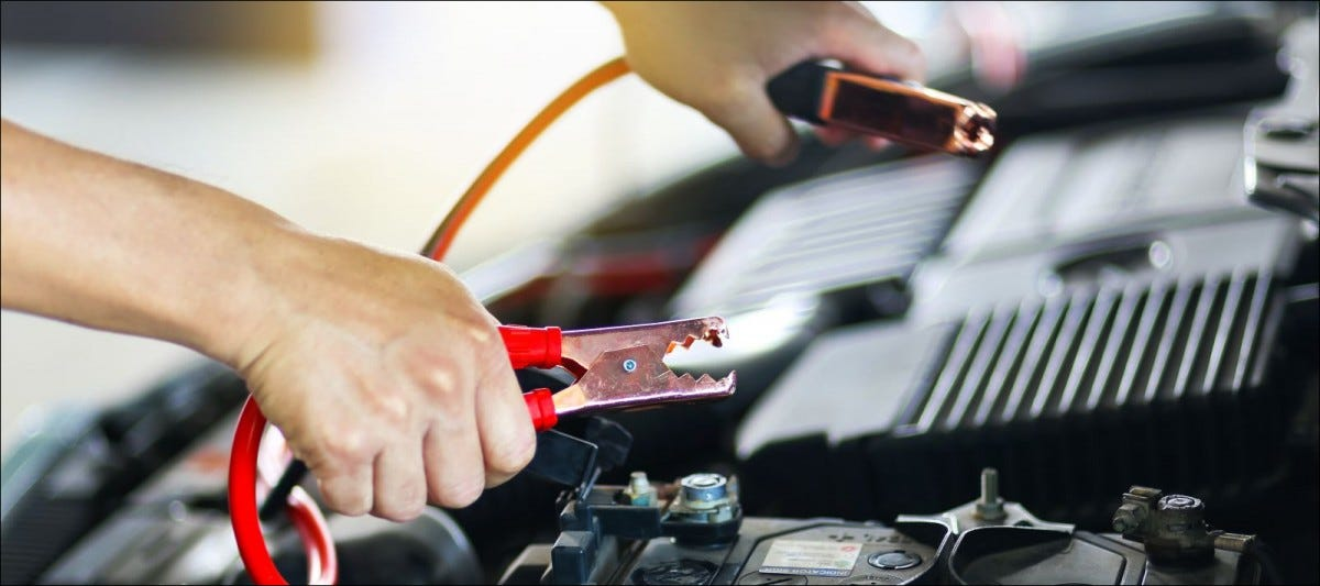 Close up of hands charging car battery with jumper cables