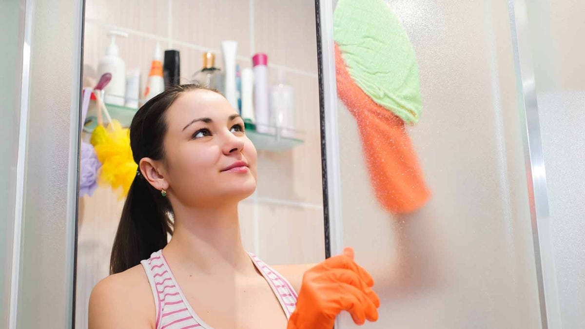 Woman wiping down a shower door with a microfiber cleaning cloth