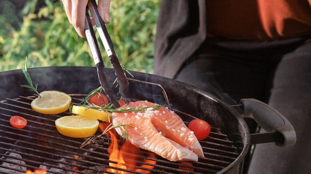 A woman grilling salmon on a traditional charcoal grill.