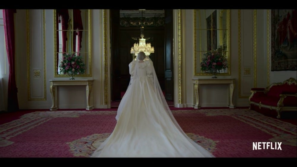 A woman in a wedding dress and long train walks into a room.