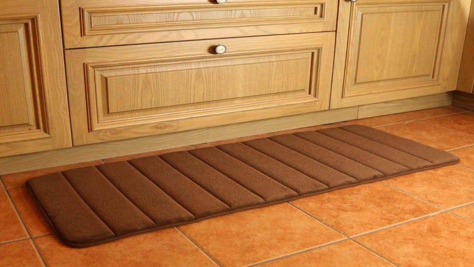 A soft brown KMAT memory foam mat on a kitchen floor.