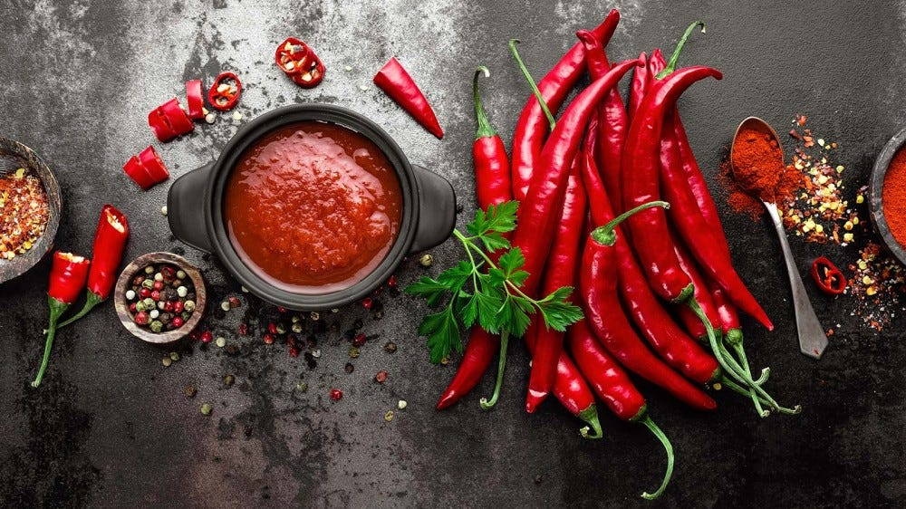 Red chilies, spices, and a bowl of hot sauce on a counter.
