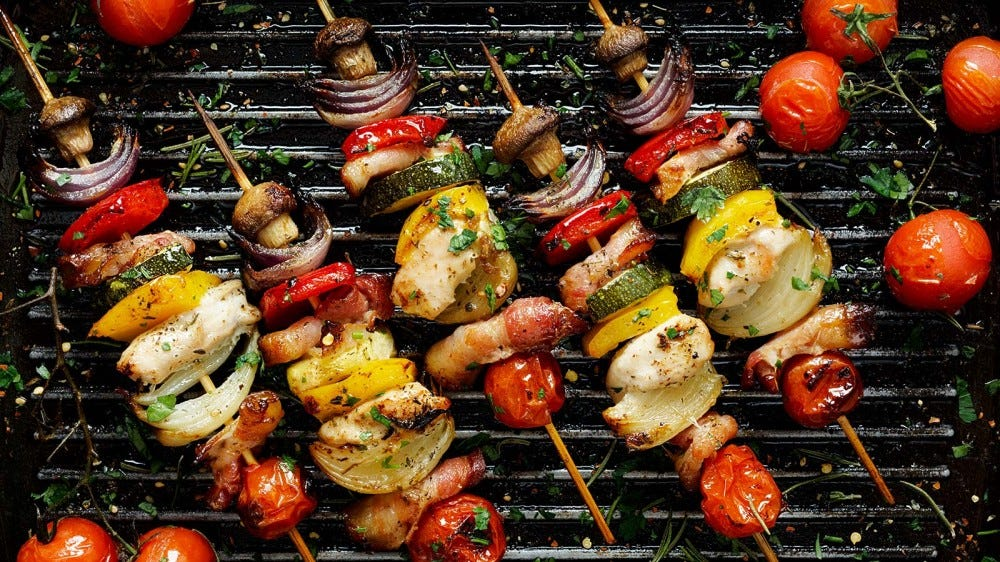 A grill loaded with seasoned vegetables on skewers.