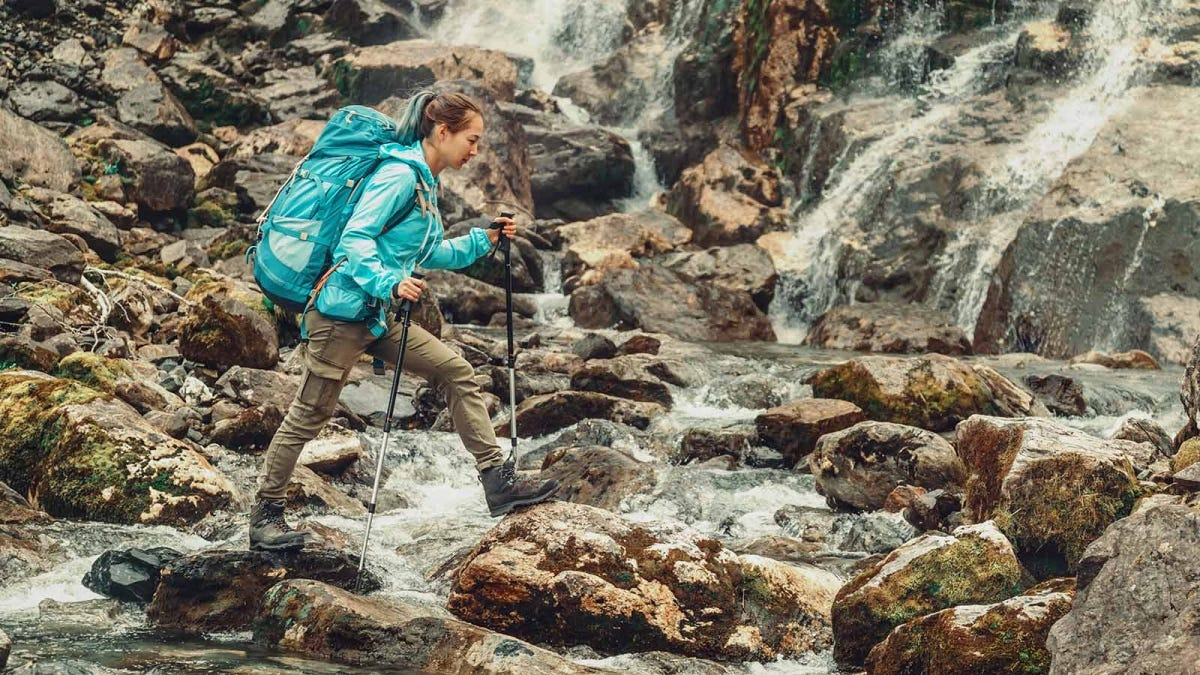 woman hiking across wet rocks using trekking poles