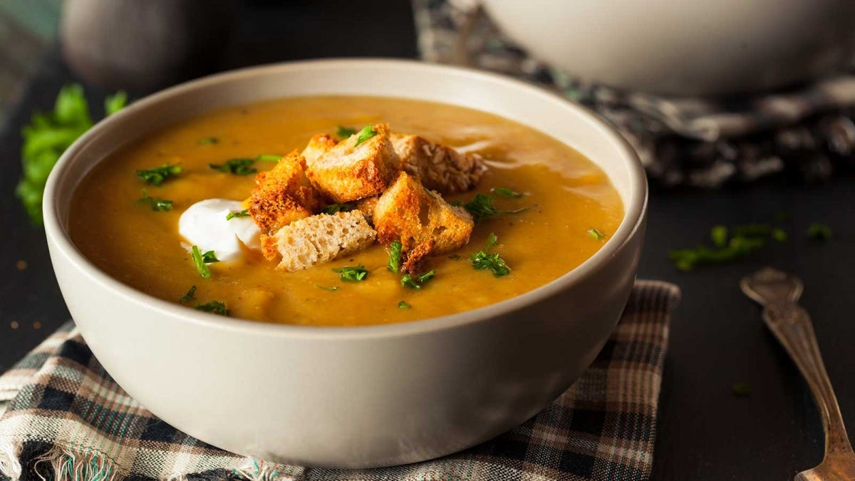 a delicious creamy squash soup with croutons and sour cream