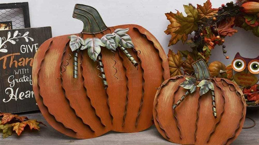 Two metal pumpkins next to an owl wreath and wooden Thanksgiving sign.