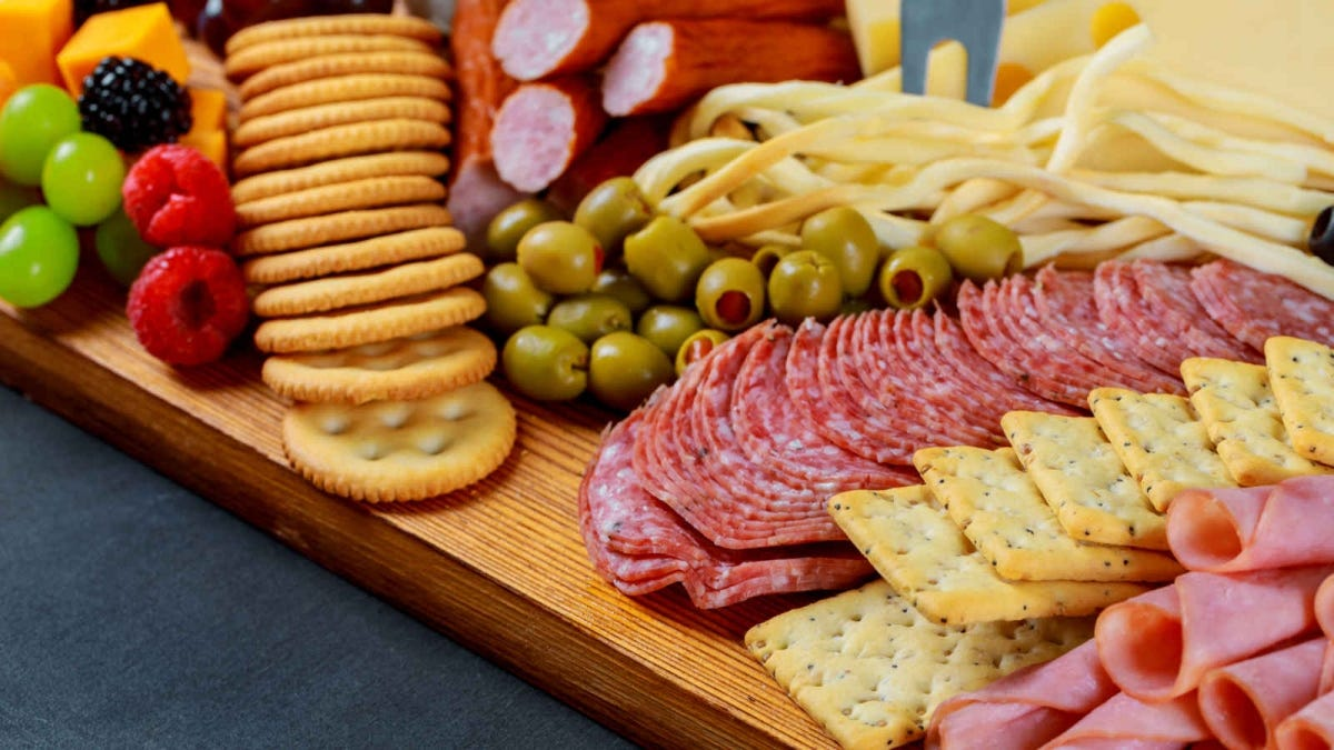 charcuterie platter with fruit, meats, cheeses, and crackers