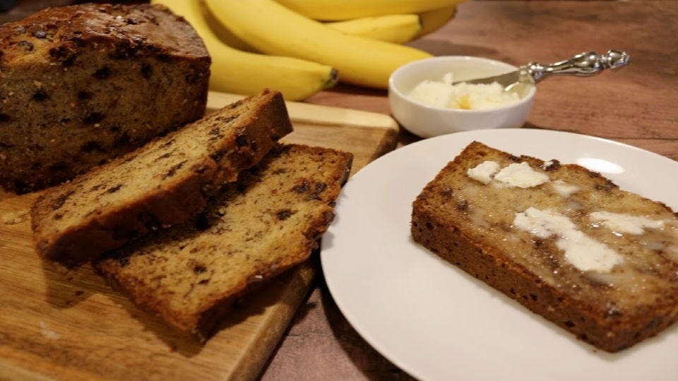A loaf of sliced banana bread on a cutting board, next to a plate with a slice of the bread covered in butter, a bowl of spreadable butter, and a bunch of bananas.