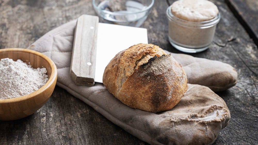 Sourdough bread along with a sour dough starter and other tools on a wooden table.