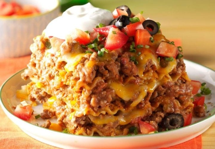 A plate of Mexican lasagna, topped with sour cream, tomatoes, and black olives.