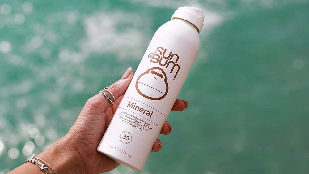 A woman's hand holding a bottle of Sun Bum Mineral Spray Sunscreen.