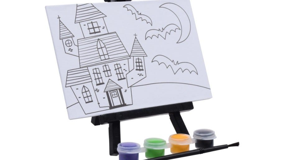 A drawing of a creepy mansion sitting on an easel with some paint containers next to it.