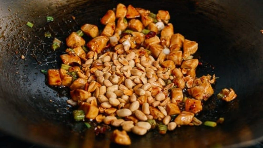 kung pao chicken and peanuts in a wok