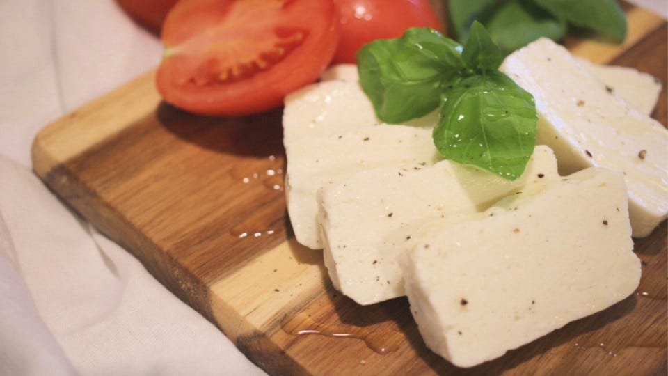 Sliced halloumi cheese on a chopping block next to some roma tomatoes and fresh basil.