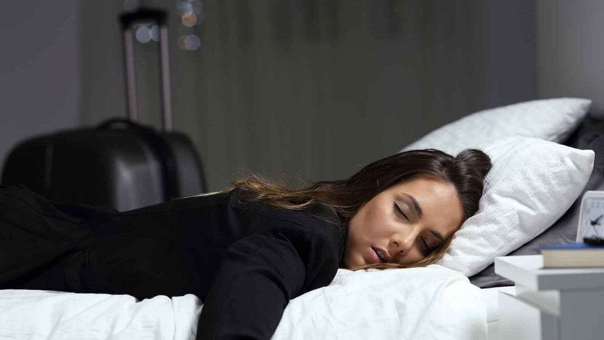 Woman, passed out from the exhaustion of jet lag, in her hotel room.