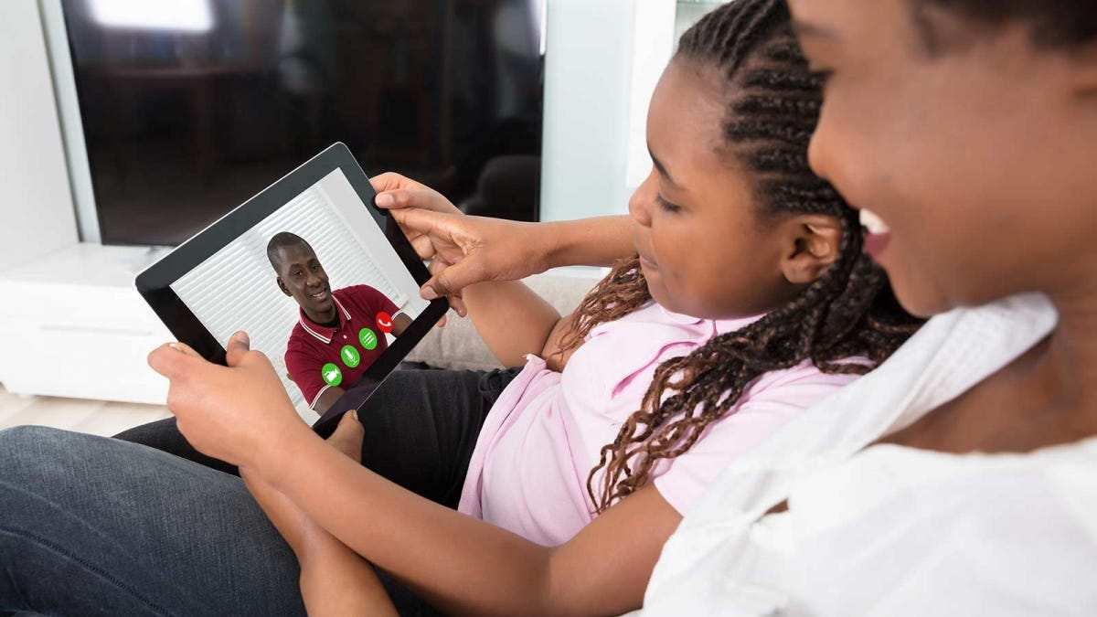 A woman holding a young girl on her lap, video chatting with a man on a tablet.