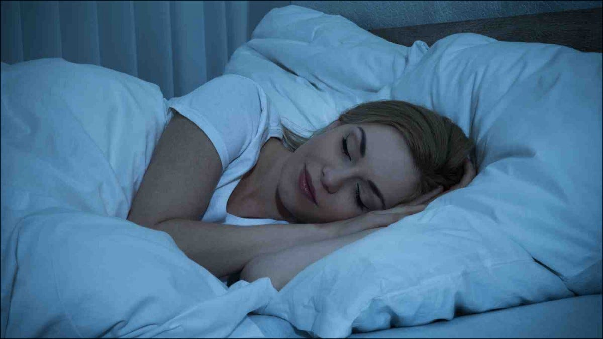Young Woman With Blanket Sleeping At Night In Bed