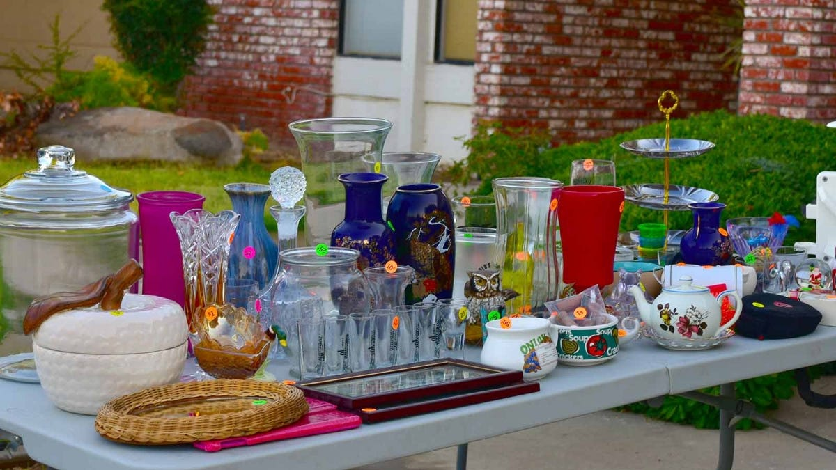 Priced glass vases and trinkets sitting on a table at a yard sale.