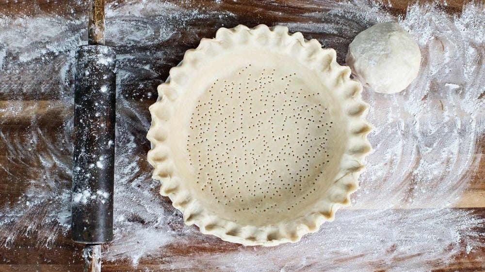 A homemade pie crust, freshly molded into the pie tin, sitting on a rustic kitchen counter.