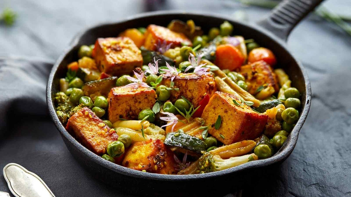 Grilled tofu and vegetables sprinkled with herbs and spices in a cast iron skillet