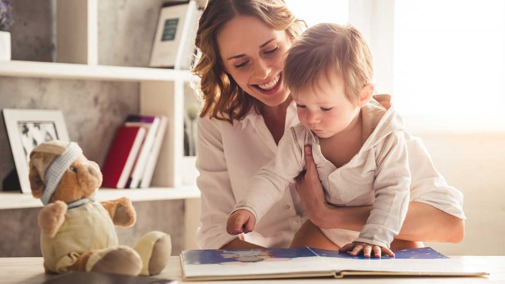 A mom looking at a baby book with her child.