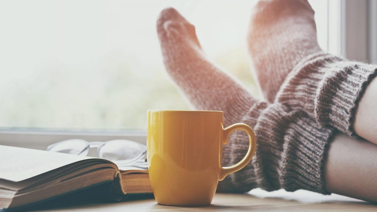A woman's feet in socks crossed at the ankles and resting on a windowsill next to an open book and coffee mug.