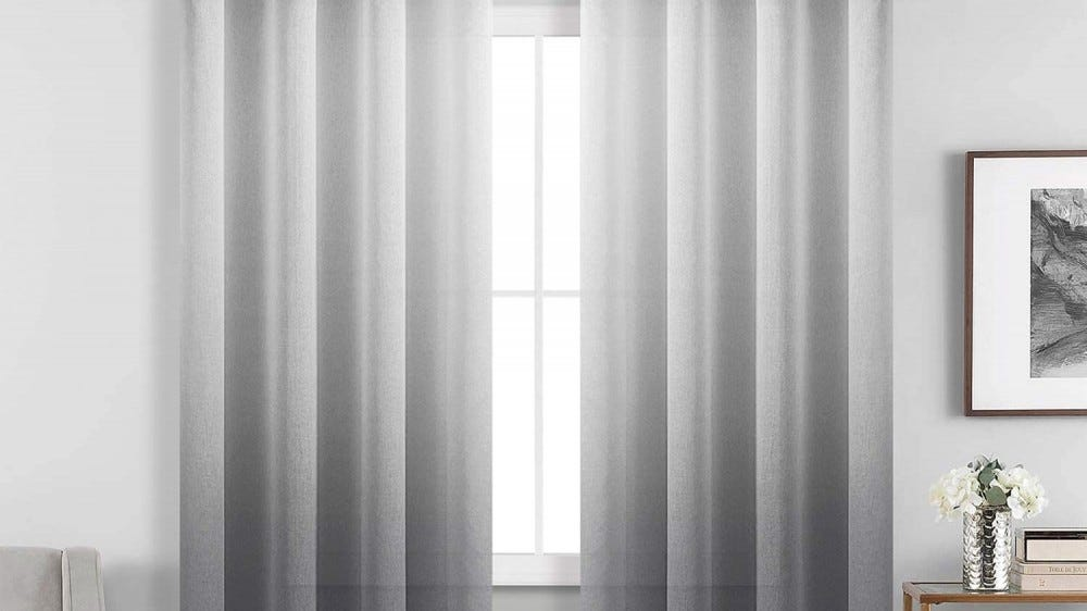 A window with sheer gray ombré curtains.