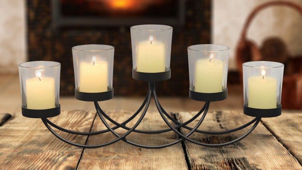 A black metal centerpiece with five lit candles.