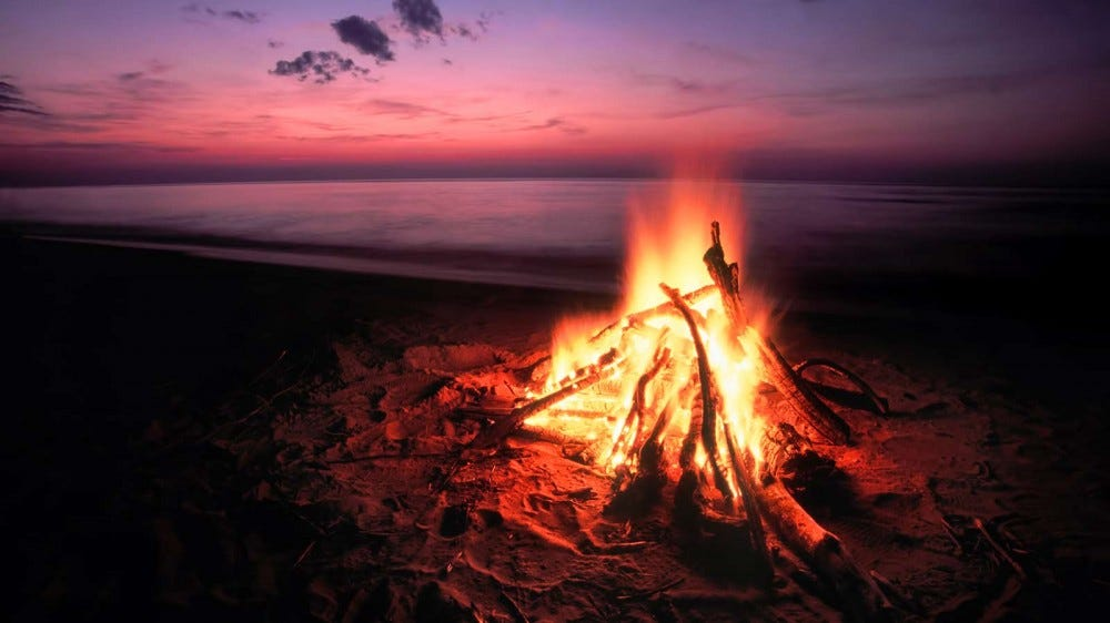 A campfire on the shores of Lake Superior, roaring against the background of sand and the distance sunset.