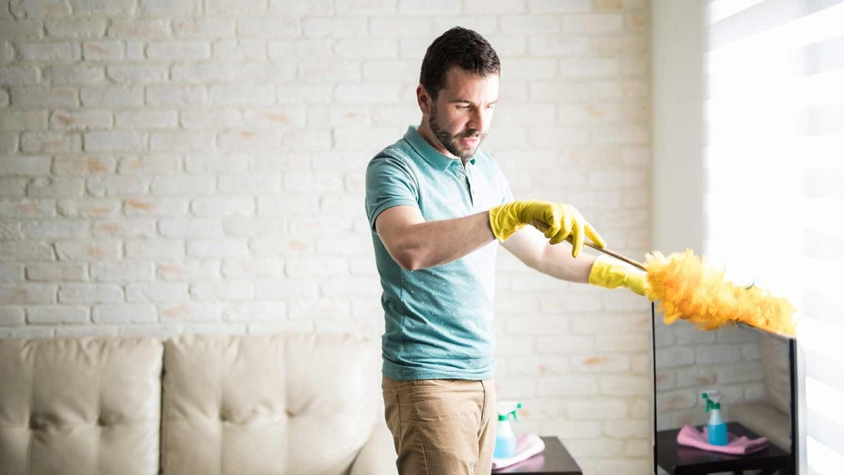 Man dusting the top of his television with a feather duster
