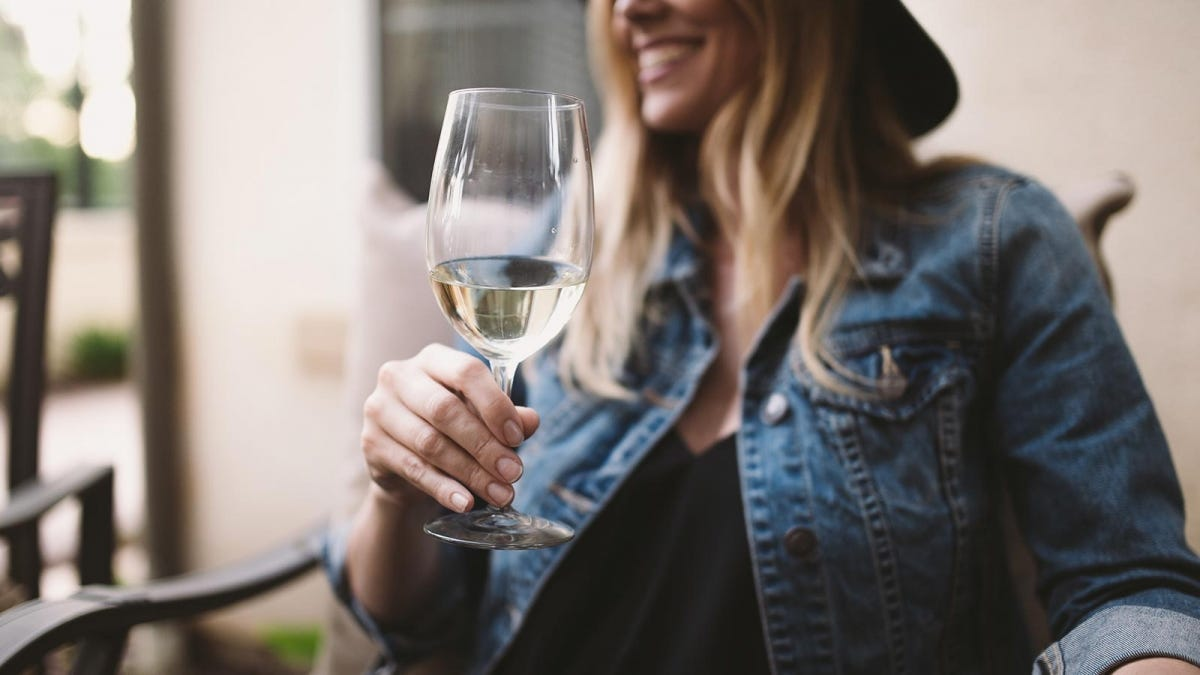 A woman drinking a glass of white wine on her patio.