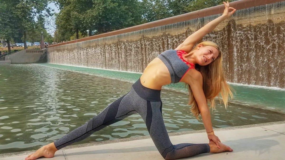 Woman doing yoga in front of a lake and waterfalls