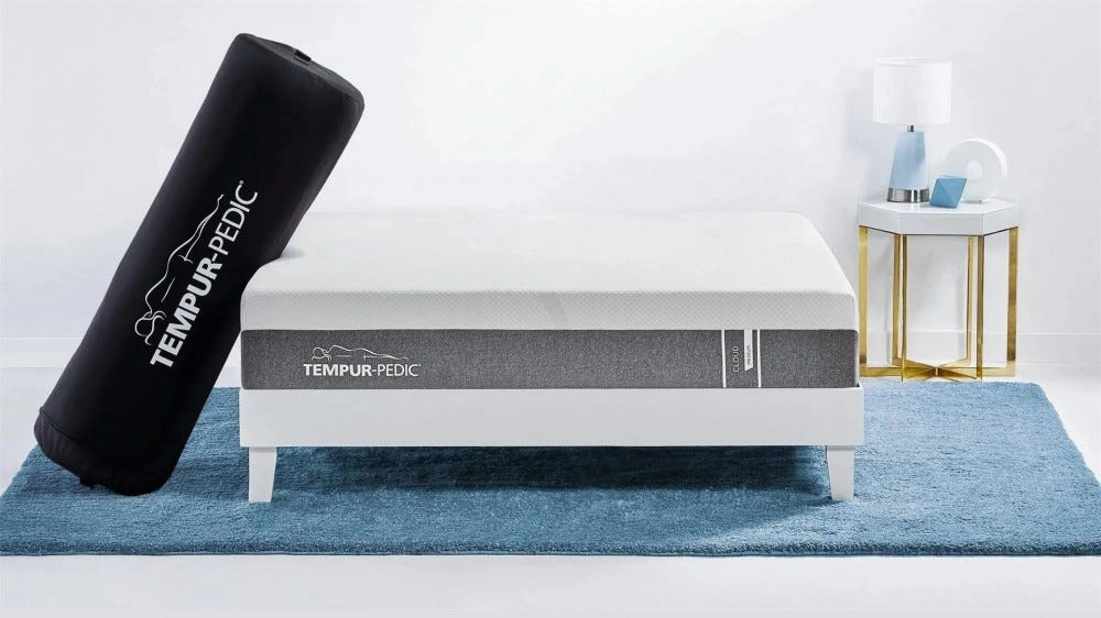 The Tempur-Pedic cloud mattress in a bag leaned up against a bed
