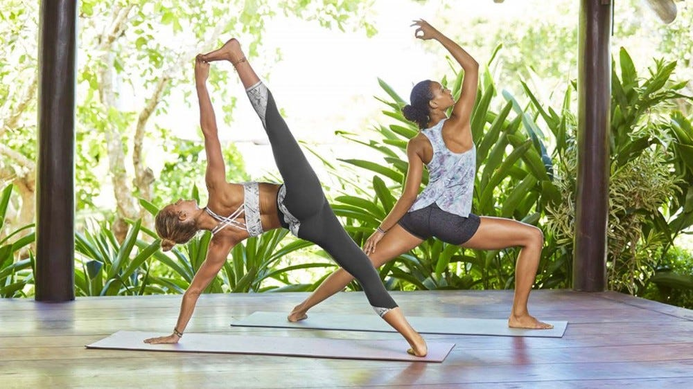 Two women in different yoga poses, wearing Athleta clothing.