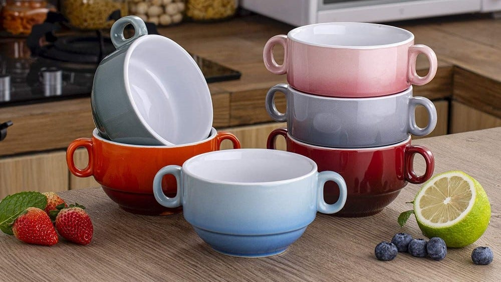 Six gradient colored soup bowls on a kitchen counter.