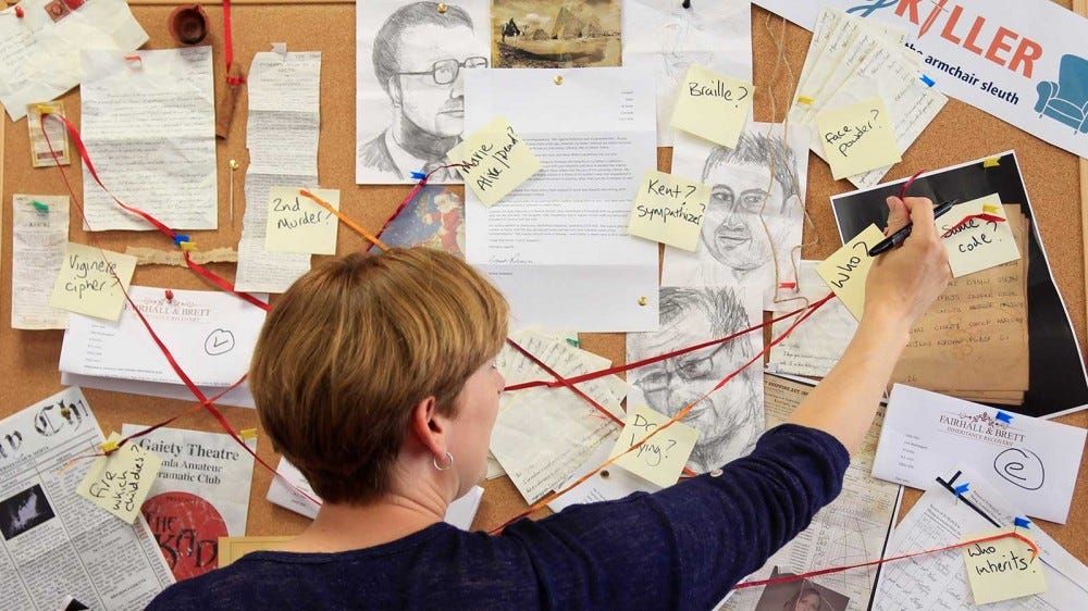 A woman standing in front of a pin board covered in clues from the Cozy Killer kit.